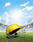 picture of cricket  - A cricket stadium with a yellow cricket helmet on an unmarked green grass pitch in the daytime under a blue sky - JPG