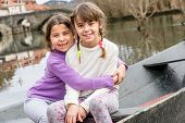 image of sisters  - Two sisters are sisters are sitting in the boat and hugging - JPG