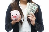 picture of million-dollar  - Business woman with a piggy bank holding dollars is a savings concept  - JPG