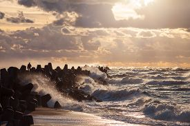 picture of breaker  - Silhouette of a man is facing storm standing on water breaker with waves and water splashes on Baltic sea while sunset - JPG