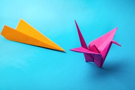 pic of float-plane  - row of colored paper origami plane crane  on a blue background