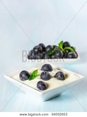 Yogurt with ripe blueberries on a wooden background.