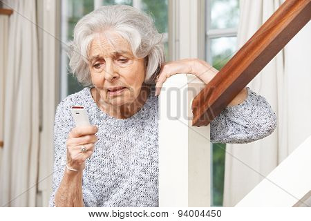 Unwell Senior Woman Using Personal Alarm At Home