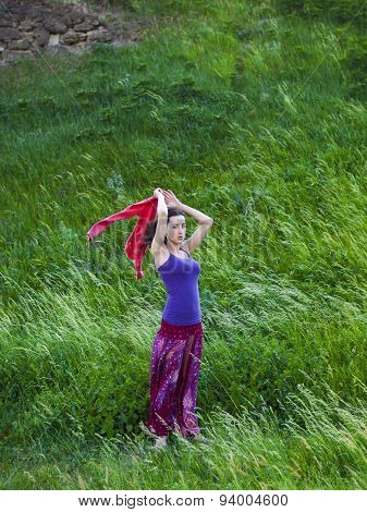 Romantic Girl Stands In A Field In The Wind.