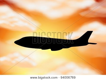 Silhouette airplane on orange sky background