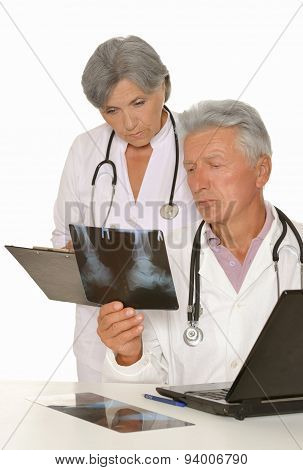 Doctors with stethoscopes looking at x-ray