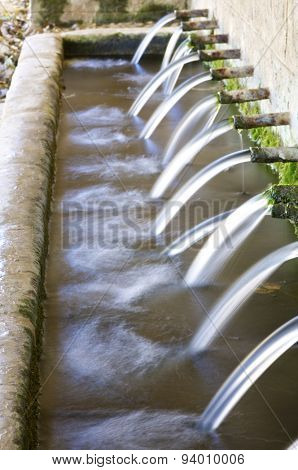 Jets of water coming through the pipes of an old fountain, Pnarroya de Tastavins, Teruel, Aragon, Spain.