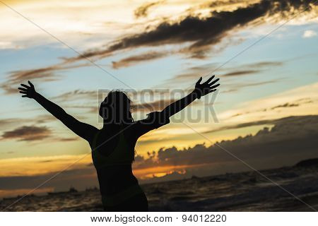 strong confidence woman open arms under the sunrise at seaside