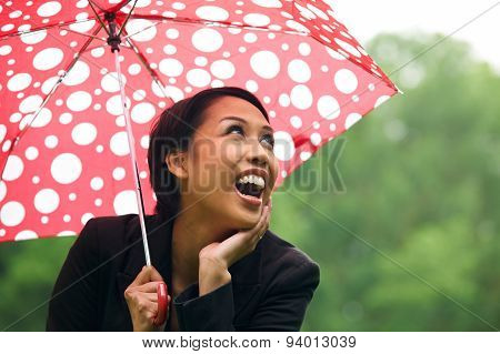 Young Woman Sheltering From Rain Under Umbrella