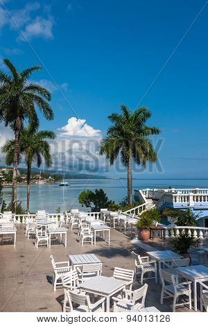 White tables and chairs  in tropical garden  on a beautiful  beach