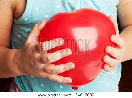 Baby Holds Red Heart Shaped Balloon
