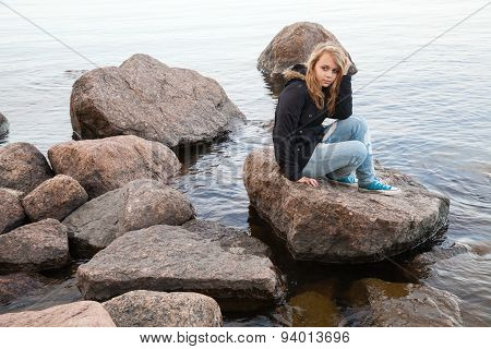 Caucasian Teenage Girl Sitting On Coastal Stones