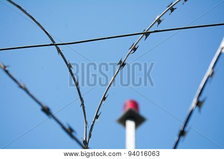 Barbed Wire And Emergency Light Against The Blue Sky, Selected Focus, Narrow Depth Of Field