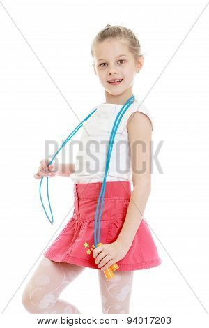 Beautiful girl schoolgirl with a skipping-rope draped over the neck