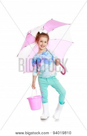 Adorable little girl with umbrella and bucket in hand