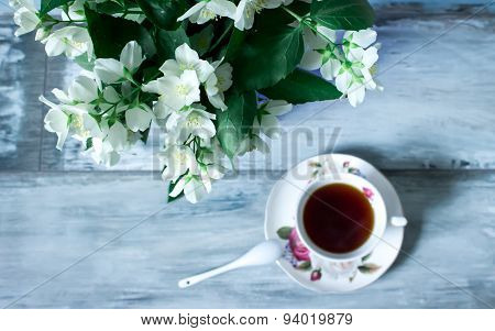 Jasmine flowers in a pot and cup of tea, rustic interior.