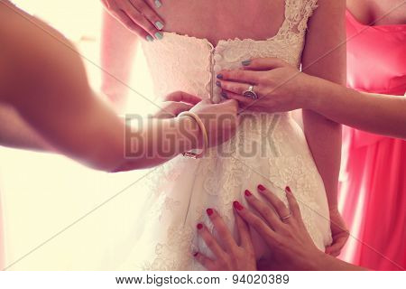 Hands Helping The Bride With The Wedding Dress