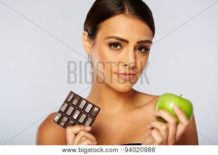Sports woman making choice between healthy apple and chocolate
