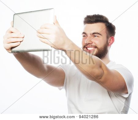 life style, tehnology and people concept: Happy selfie. Young bearded man holding tablet and making photo of himself while standing against white background