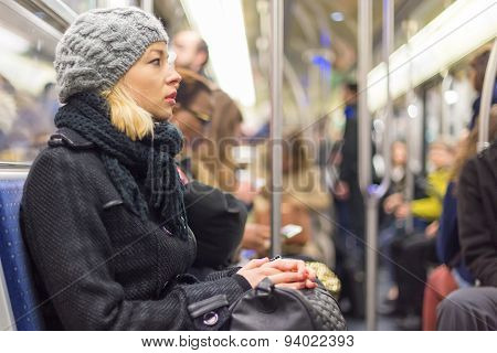 Woman traveling by subway full of people.