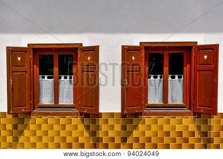 Two Old Windows With Opened Shutters On White Wall And Yellow Tiles