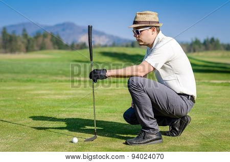 Golfer looking golf shot with club