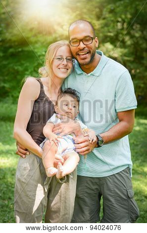 Happy Interracial Family Is Enjoying A Day In The Park With Adopted Son.