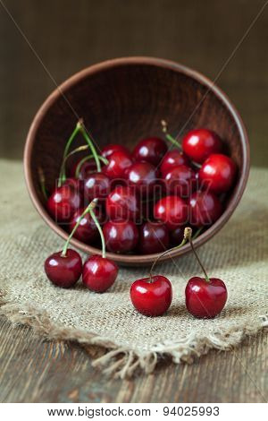 Cherries fresh organic vegetarian superfoods in clay dish on vintage kitchen table background