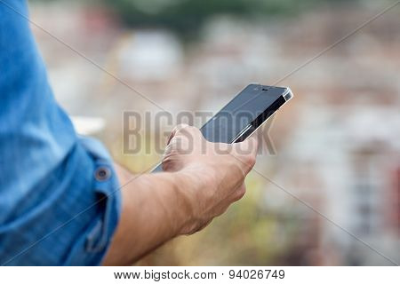 Man Hand Holding Mobile Phone In The City.