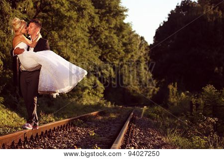 Groom Carrying His Bride On A Railroad