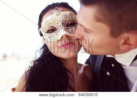 Groom Kissing His Bride. Bride Wearing Venezian Mask