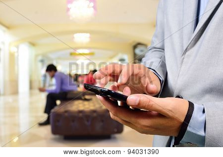 Business Man Using Mobile Phone In Modern Building Hallway