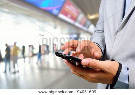 Business Man Using Mobile Phone In Modern Train Station