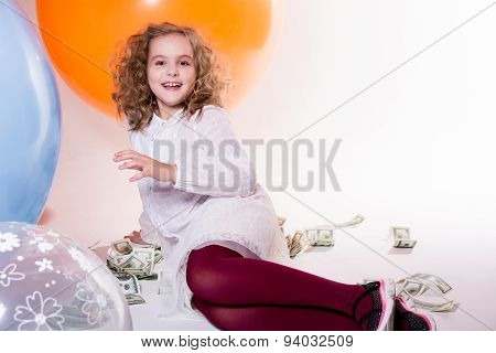 Young Cheerful Girl Sitting And Lying Around Dollars And Big Rubber Balloons