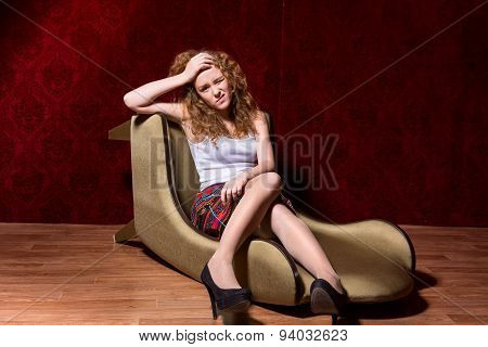 Unhappy Young Girl Sitting On A Chair On A Red Background