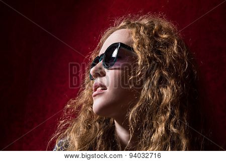 Close-up Portrait Of Beautiful Pensive Girl With Curly Hair Wearing Sunglasses