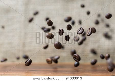 Coffee Beans Falling Down On A Wooden Plank