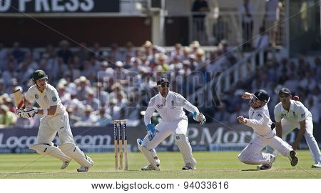 LONDON, ENGLAND - July 19 2013: Steven Smith hits the ball and watches on as it passes a diving Ian Bell during day two of the Investec Ashes 2nd test match, at Lords Cricket Ground on July 19, 2013