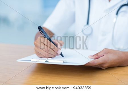 Doctor holding clipboard with file in hospital room