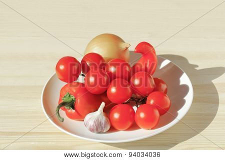 Pepper, tomato, onion and garlic in the dish on a table