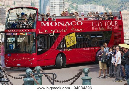 People enjoy sightseeing tour on the red Monaco city tour bus in Monaco.