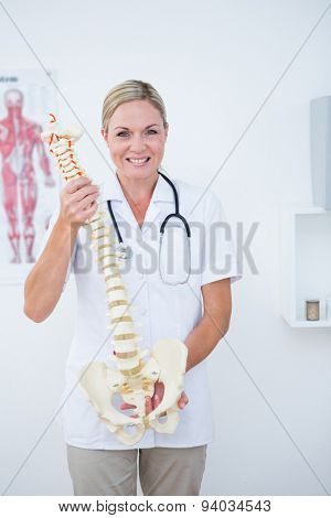 Smiling doctor showing anatomical spine in clinic