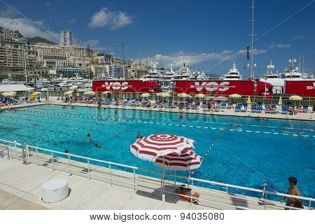 People swim and sunbathe at the open air public swimming pool in Monaco.