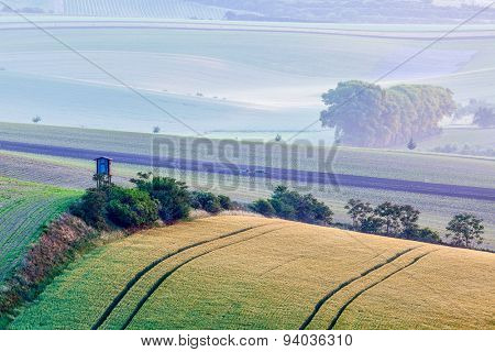 Rural Europe background - Moravian rolling landscape with hunting tower shack in early morning on sunrise. Moravia, Czech Republic