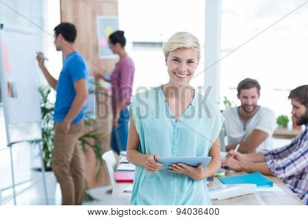 Pretty blonde businesswoman using tablet in the office