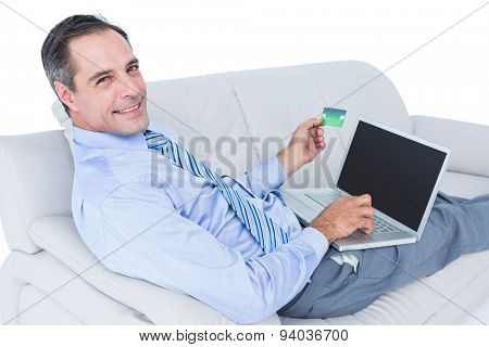 Smiling businessman lying ona sofa holding a card and laptop against a white wall
