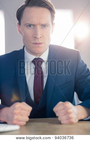Angry businessman with closed fists looking at camera in his office