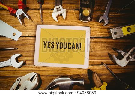 The word yes you can! and tablet pc against blueprint