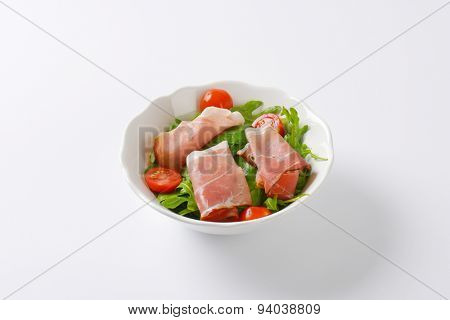 bowl of dried pork ham, rucola and spinach leaves and halved cherry tomatoes on white background