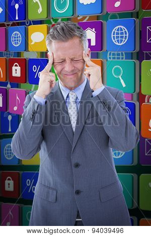 Businessman with headache against green background with vignette